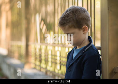 Portrait of a sad boy leaning against metal railings - Stock Photo