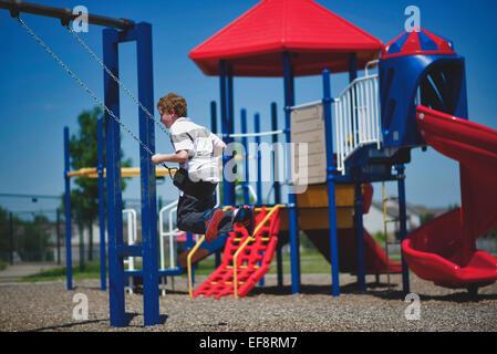 Boy (10-11) swinging on swing on playground - Stock Photo