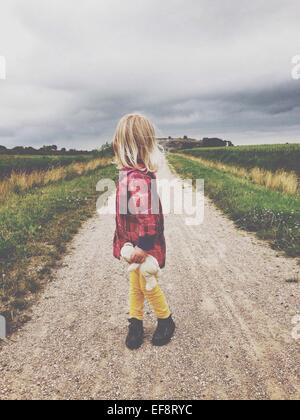 Blonde girl (2-3) standing on dirt road, holding teddy bear, looking over shoulder - Stock Photo