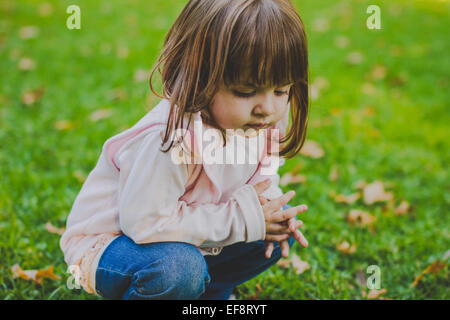 Portrait of girl (2-3) crouching on grass - Stock Photo