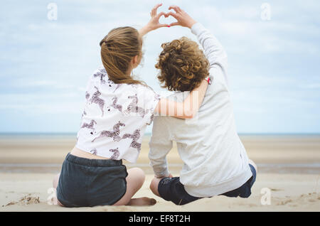 Two children sitting on beach making heart shape with their hands - Stock Photo