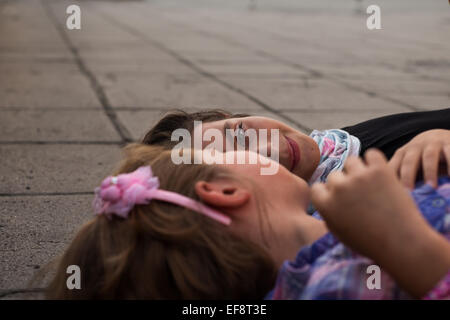 Two girls lying on ground talking - Stock Photo
