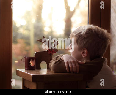 Boy (6-7) looking out of window - Stock Photo