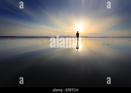Boy walking on beach at sunset - Stock Photo