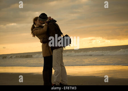 Couple embracing and kissing on beach at sunset - Stock Photo