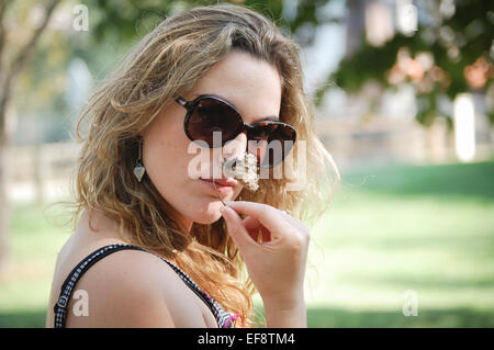 Portrait of young woman smelling flower - Stock Photo