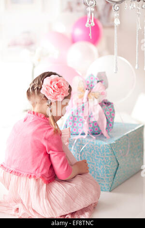 Girl sitting in front of a stack of birthday gifts - Stock Photo