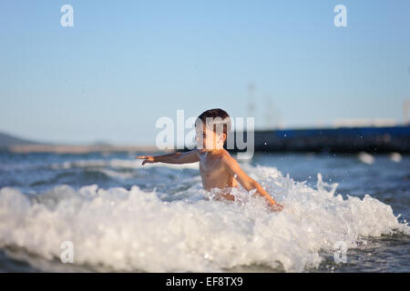 Boy playing in the sea - Stock Photo