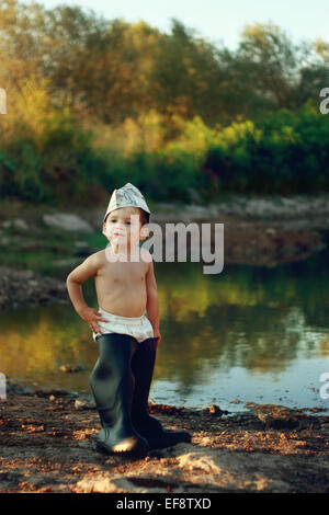 Boy (18-23 months) wearing huge rubber boots and paper hat standing by pond - Stock Photo