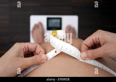 Pregnant woman measuring belly on weight scale - Stock Photo