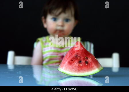 Watermelon slice in front of a baby girl sitting in a high chair - Stock Photo