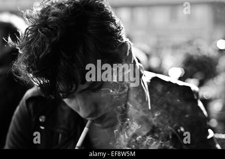 Young man smoking cigarette looking down - Stock Photo