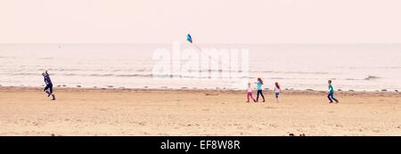 Woman running along beach with a kite, followed by four children, Norfolk, England, UK - Stock Photo