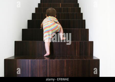 Baby climbing wooden stairs - Stock Photo