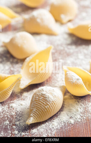 raw pasta and flour on table - Stock Photo
