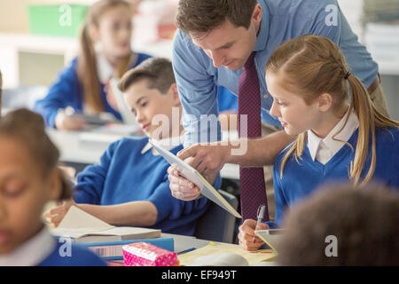 Teacher with his pupils in classroom using tablet pc - Stock Photo