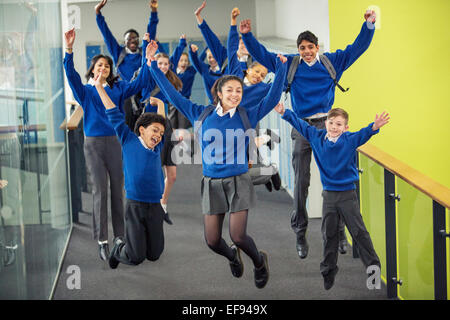 Enthusiastic high school students wearing school uniforms smiling and jumping in school corridor - Stock Photo