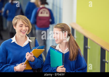 Two smiling female students wearing school uniforms walking through school corridor - Stock Photo