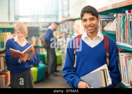 Portrait of teenage student standing with books in college library - Stock Photo