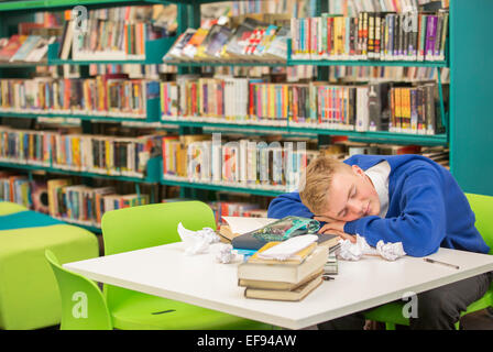 Exhausted student sleeping on table in library - Stock Photo