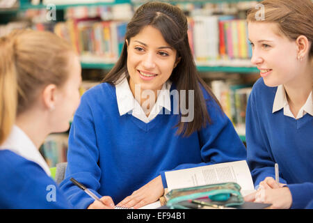 Three female students sitting in library and smiling - Stock Photo