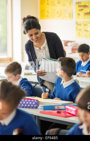 Teacher and elementary school children in classroom during lesson - Stock Photo