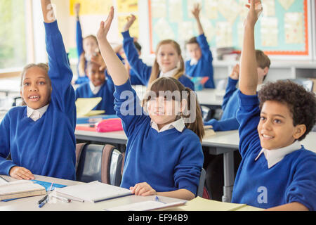 Elementary school children wearing blue school uniforms raising hands in classroom - Stock Photo