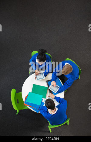 Overhead view of high school students sitting at round table with digital tablets - Stock Photo