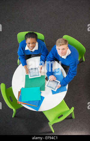 Overhead view of teenage boy and girl sitting at round table with digital tablets, looking at camera - Stock Photo
