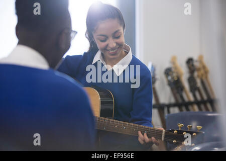 Students playing acoustic guitar in classroom - Stock Photo