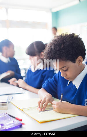 Schoolboy drawing in notebook at desk in classroom, girls in background - Stock Photo