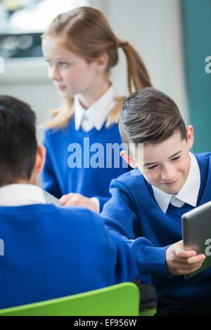 Elementary school children wearing blue school uniforms in classroom - Stock Photo