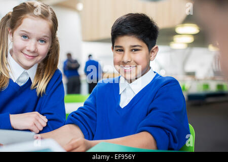 Portrait of smiling school children wearing blue school uniforms sitting at desk - Stock Photo