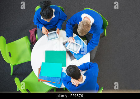 Overhead view of three students with digital tablets at round table - Stock Photo