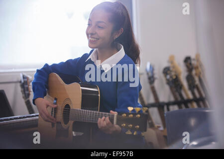 Smiling female student playing acoustic guitar - Stock Photo