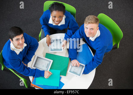 Overhead portrait of three students with digital tablets sitting together at round table - Stock Photo
