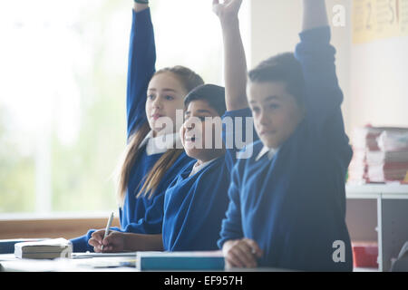 Primary school children in classroom raising arms - Stock Photo