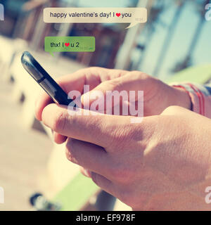 a young man sending a text message with a smartphone with the text Happy valentines day, I love you - Stock Photo