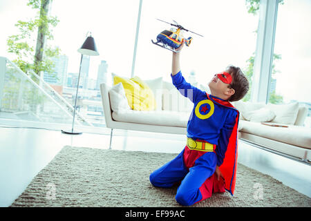 Superhero boy playing with toy helicopter in living room - Stock Photo