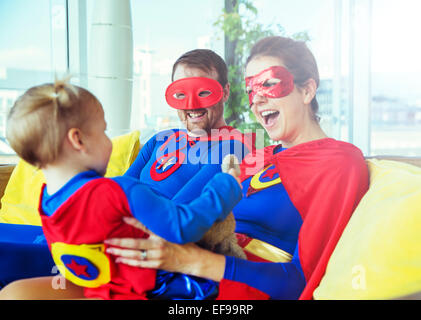 Superhero parents playing with daughter on living room sofa - Stock Photo