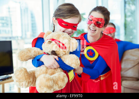 Superhero mother and daughter playing with teddy bear - Stock Photo