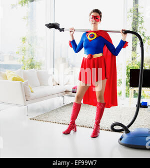 Superhero holding vacuum in living room - Stock Photo