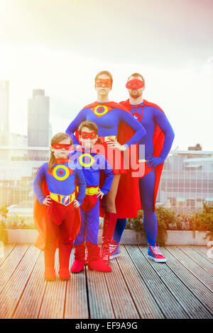 Superhero family standing on city rooftop - Stock Photo