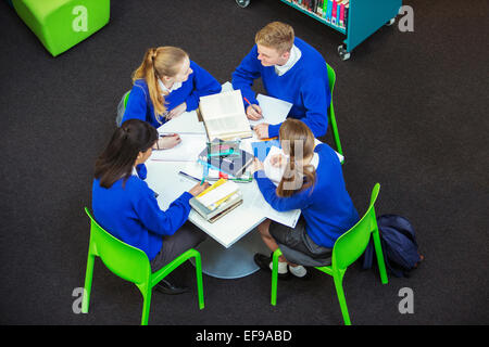 Overhead view of four students doing their homework at round table - Stock Photo