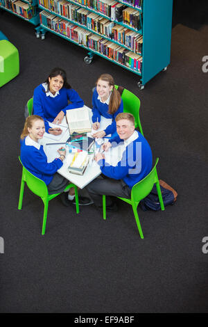 Overhead view of four students doing their homework at round table, looking at camera - Stock Photo