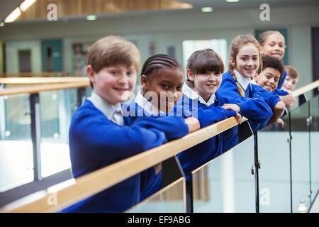 Portrait of elementary school children wearing blue school uniforms standing in school corridor - Stock Photo