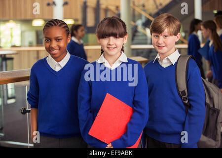 Portrait of three elementary school children wearing blue school uniforms standing in corridor - Stock Photo
