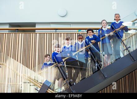Portrait of elementary school children wearing blue school uniforms standing on steps in school - Stock Photo