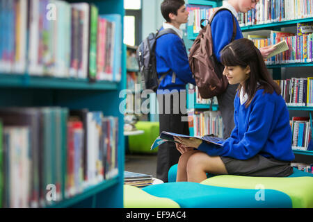 Students reading books in library - Stock Photo