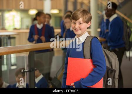 Portrait of elementary school boy wearing blue school uniform standing in school corridor - Stock Photo